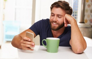 Young Man Drinking Coffee And Using Mobile Phone At Home