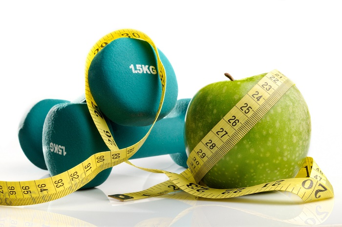 healthy apple, measuring tape and dumbbells for healthy living isolated