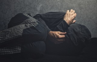 Drug Addict laying on the floor in agony, having an addiction crisis