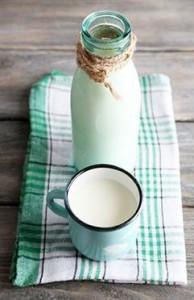 Glass bottle of milk on wooden background